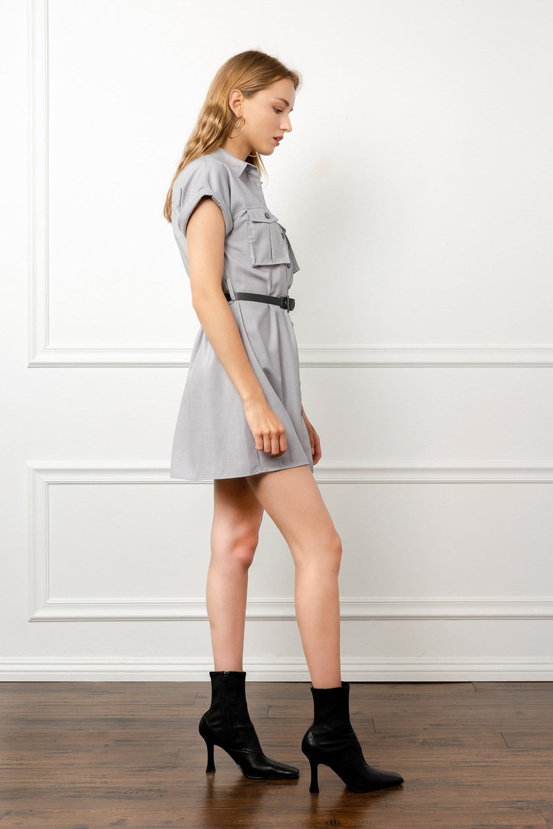 Side shot of model wearing grey utility shirt dress with black belt by j.ing