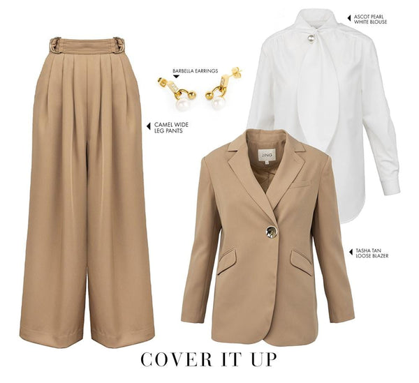 tan oversize blazer, tan wide-leg pants, white long sleeve blouse with tie and pearl