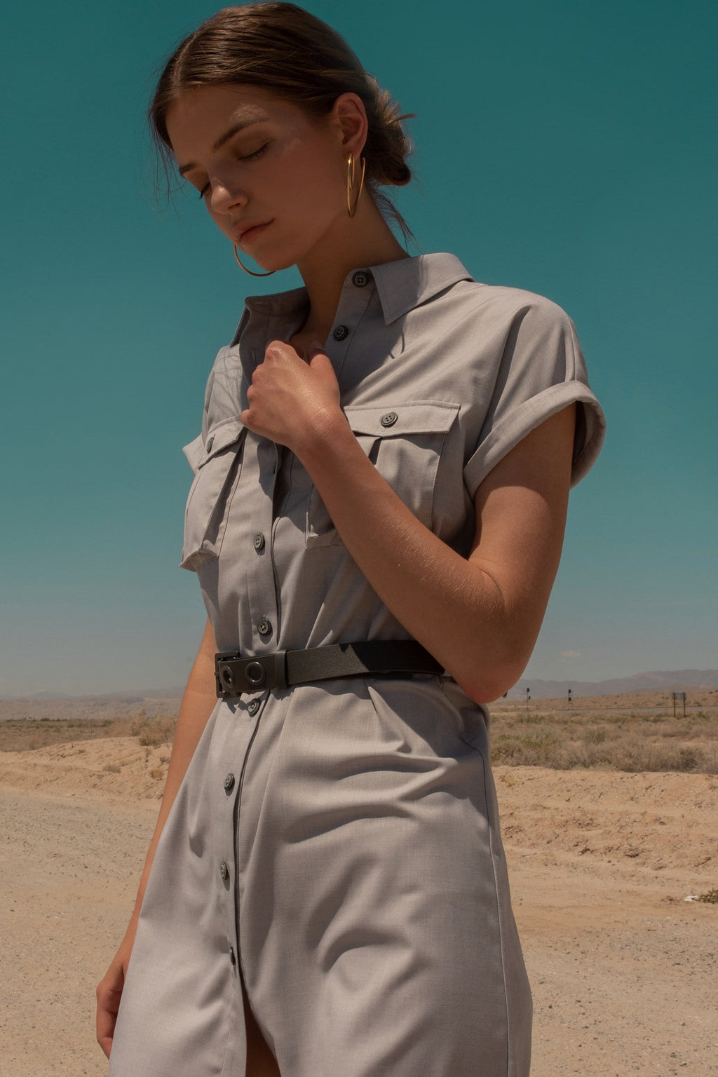 brunette model in desert wearing grey utility dress by J.ING