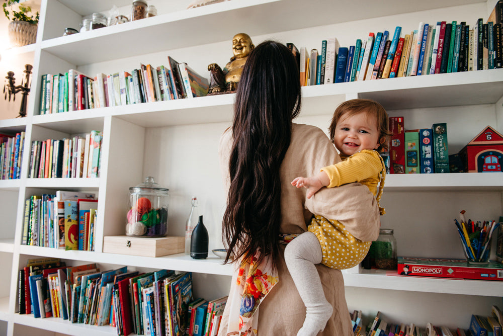 Libby holding her daughter in front of a bookcase where a diffuser is sitting