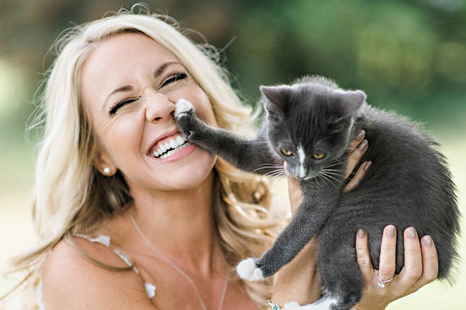 headshot of Crystal laughing outside while holding a gray kitten
