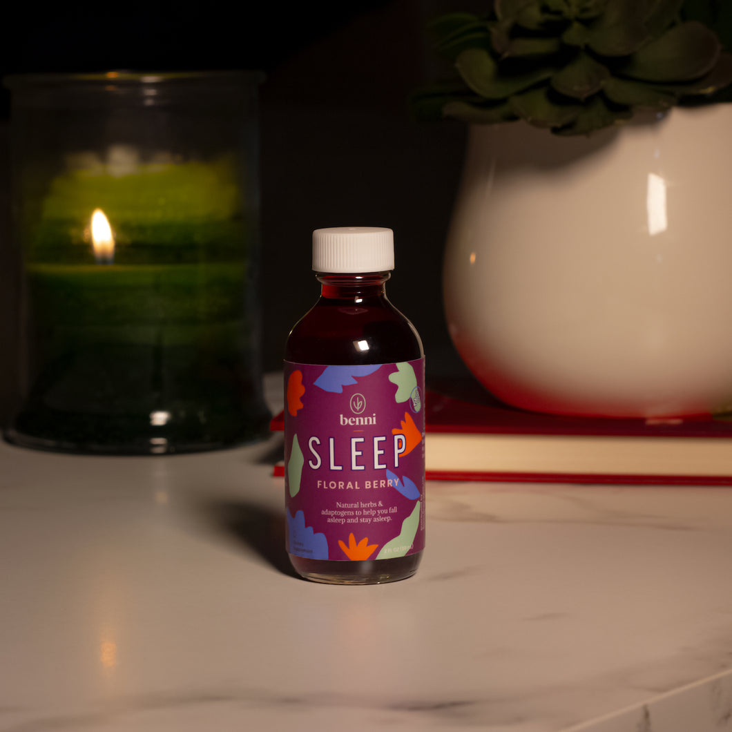 The Sleep shot on a bedside table in front of a candle, book, and plant