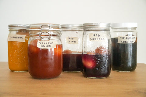 natural dyes in mason jars with wooden eggs inside