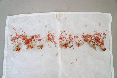 dried marigold, saffron, and chamomile are scattered on top side of linen