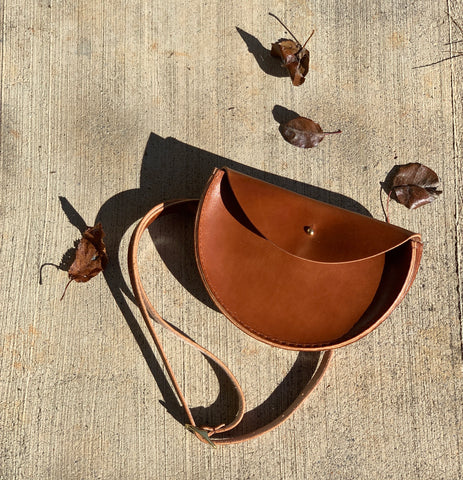 a handmade cognac colored half moon bag laying on the ground with leaves