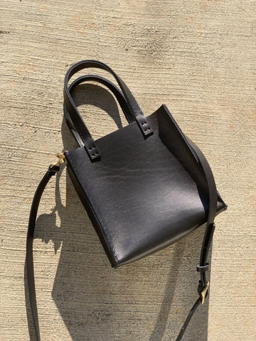 a handmade black leather tote bag with crossbody straps