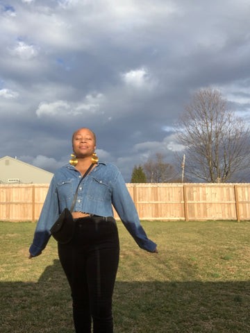 black women with shaved head standing with her eyes closed taking a breath of fresh air in her sister's backyard under a blue sky