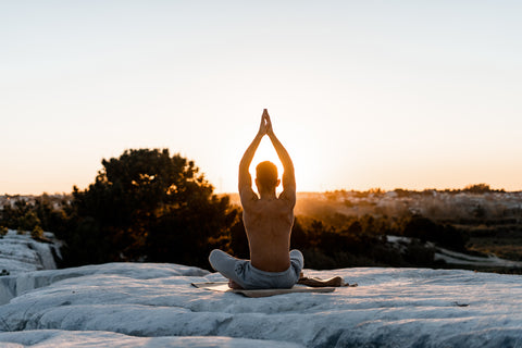 Man Practicing Yoga at Sunset Benefits