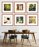 grid gallery wall collection of 6 boho chic light wooden square framed art prints with matboards arranged above a simple dining room table. Art prints included are pug and the pie, ripped poters, long grass and perch on a pattina.
