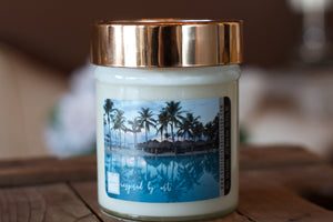 """Tropical Vacation,"" art by Shanna Koltz on a Soy candle with crackling wooden wick in a 10oz Glass Jar with a shiny lid"