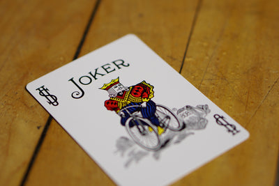 Closeup of the Joker card sitting on a hardwood floor