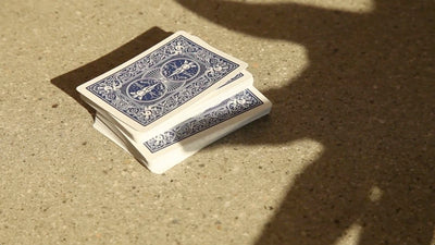Closeup of deck of cards on the ground, a shadow of a hand is pushing half the deck over