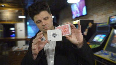 Magician holding a deck of cards with the Ace hovering in front of it.