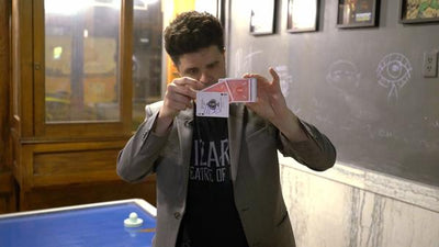 Another shot of the magician holding a deck of cards with one hovering in front.