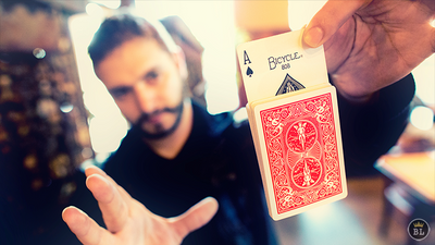 Man holding up a deck of cards via one card sticking out the top of the deck.