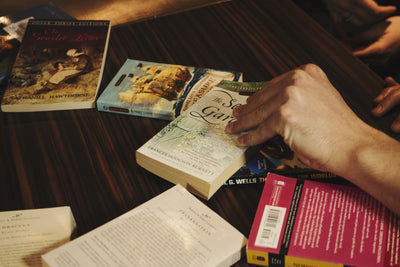 Photo of hand grabbing a book from a range of different titles on the table