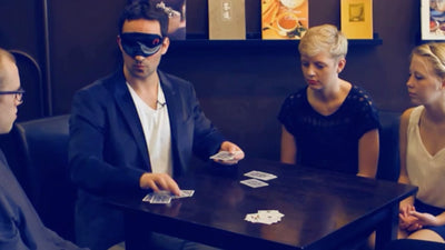 Rick performing Binary Code blindfolded for spectators at a table.