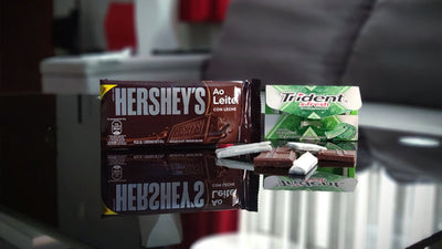 Hershey's bar and Trident package sitting side by side with some pieces of gum and chocolate sitting in front of it.