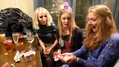 Woman holding a block of ice in her hands in front of her with a look of shock on her face. Two other women beside her are staring at her hands looking shocked as well.