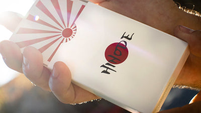 Closeup of Hinode box with cards sticking out the top in a mans hands
