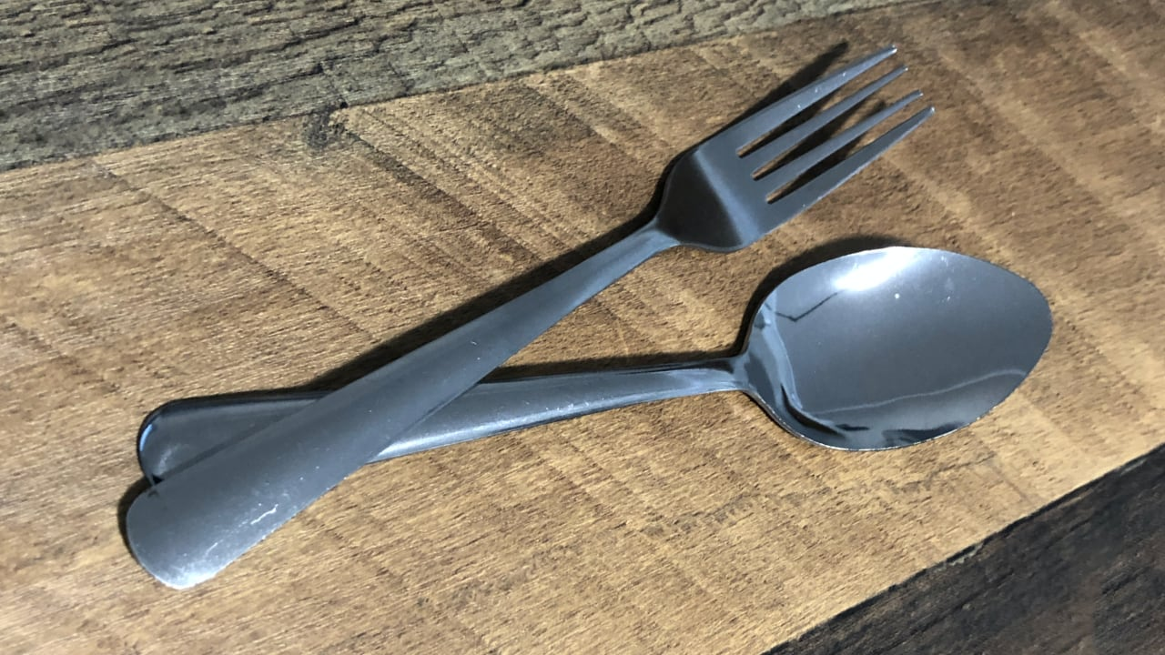 Fork and spoon on wooden table with fork handle overlapping bottom of spoon handle