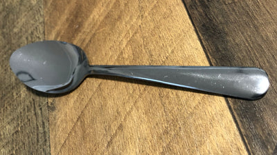 Stainless steel spoon sitting on wooden table