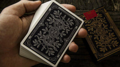 Closeup of hand holding Monarch deck face down, displaying the back of the cards.