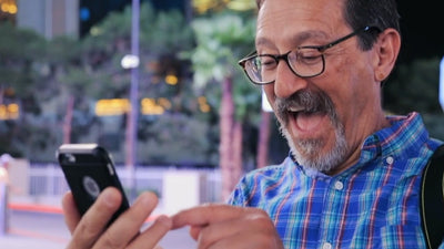 Man with glasses and beard looking at his phone with lots of excitement after finding out it was his phone in his hands