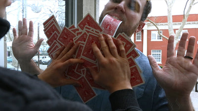 View from inside of somebody holding cards spread across the window as Cody pulls a card through the glass with his teeth, his hands are visible.