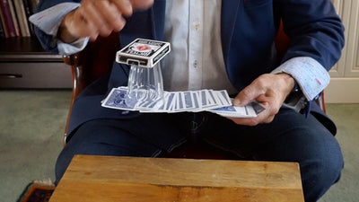 Closeup of one hand holding a spread out pile of cards that is also balancing an empty glass and deck of cards on the end not in the hand.