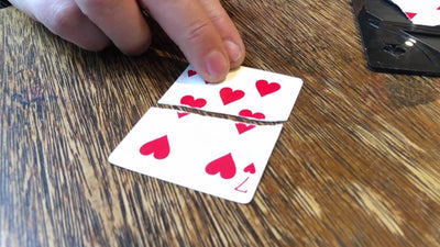 Closeup of the 7 of Hearts card torn across the middle and a hand pushing the pieces together