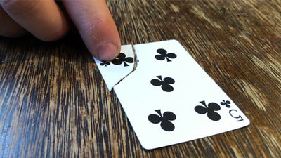 Closup of 5 of Clubs card with a corner torn off and a finger pushing the pieces together to show they match.