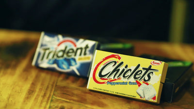 Pack of Chiclets and Trident on table. Chiclets are in focus and at the front.