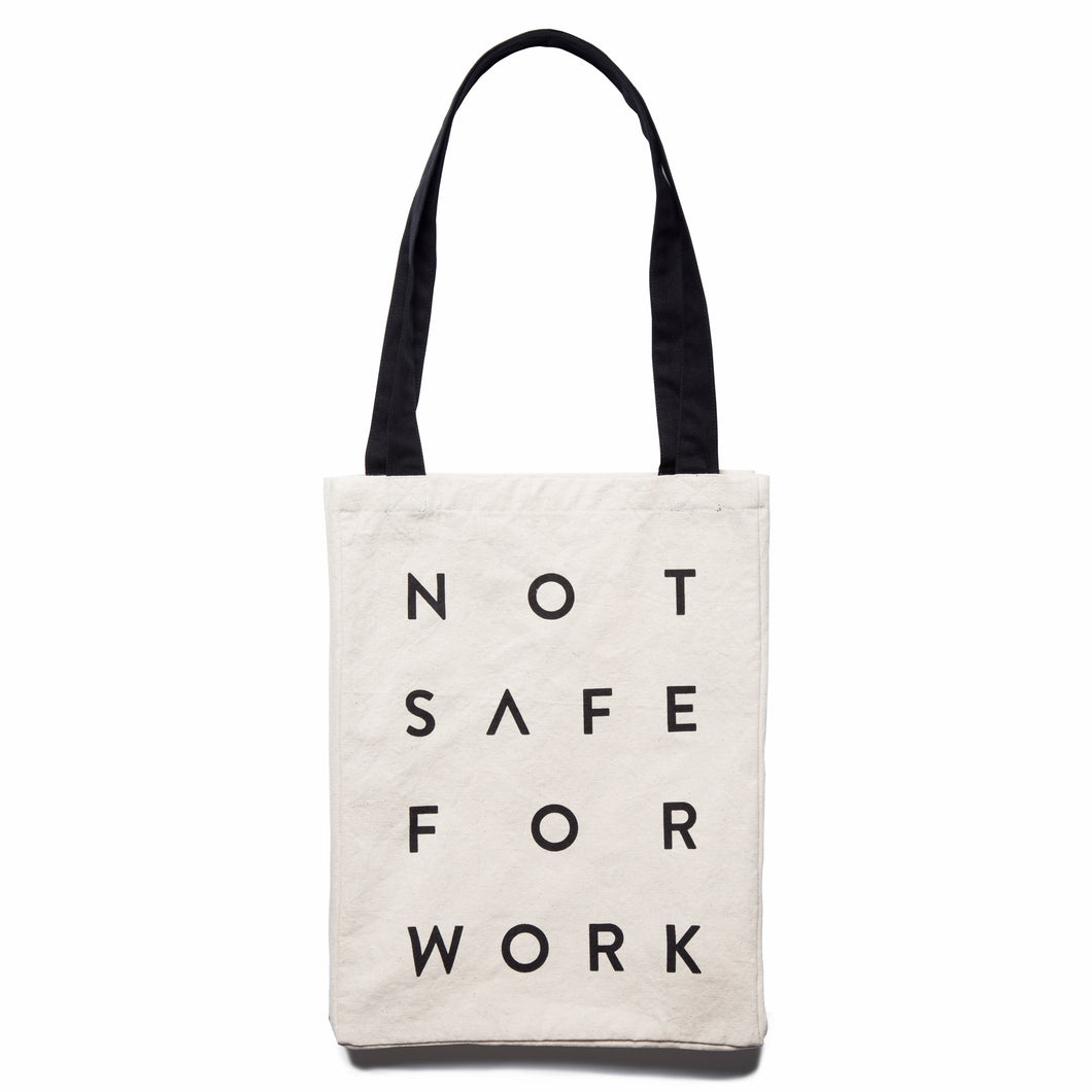 Not Safe For Work black word print on white canvas with black straps.