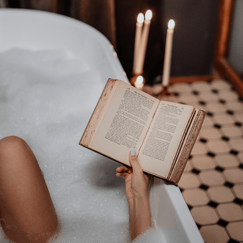 Woman in bath reading book