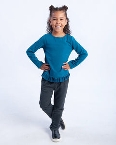Girl wearing houndstooth printed pants and a teal coloured long-sleeve tee that has teal tulle with gold glitter around the hem.