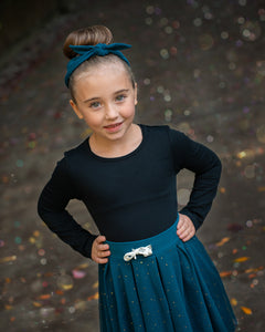 Girl wearing a teal headband and black long-sleeve tee tucked into a teal tulle skirt.