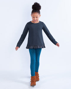 Girl wearing long-sleeve, grey houndstooth printed pullover with a peplum ruffle hem and teal leggings with gold polka dots.