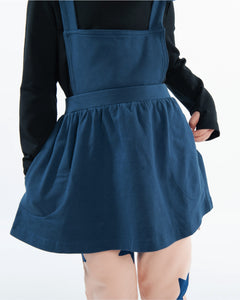 Girls navy pinafore dress featuring a softly gathered full skirt with pockets and ruffled straps that criss-cross at the back.