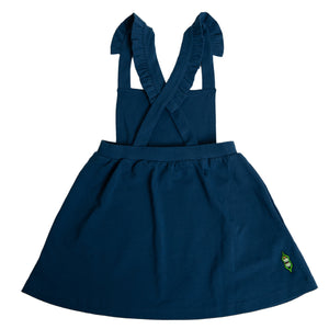 Back view of girls navy pinafore dress featuring a softly gathered full skirt with pockets and ruffled straps that criss-cross at the back.