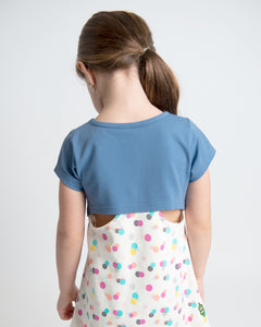 Girl wearing short-sleeve tunic with a round hem and navy on the top and a colourful stamp print on the bottom. Cut-out details on the back.