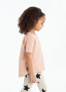 Side view of a blush pink coloured short-sleeve tee and star-printed leggings modeled on a girl.