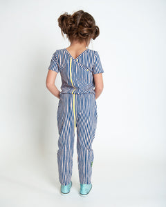 Back view of girl wearing short-sleeved navy and yellow stripe printed romper for girls with a crossover design at the back neckline and drawstring at waist.