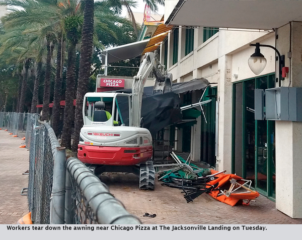 Workers tear down the awning near Chicago Pizza at The Jacksonville Landing on Tuesday.