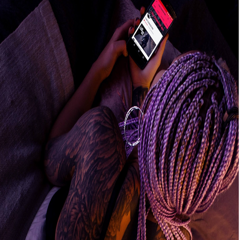 Woman holding cell phone with medium sized purple individual braids in her hair