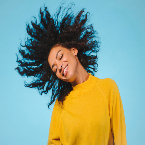 African American woman wearing a yellow shirt with natural hair swinging her hair around in a circle