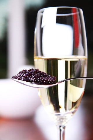 a glass of champagne and caviar