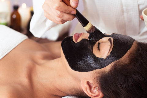 putting the caviar facial mask on face