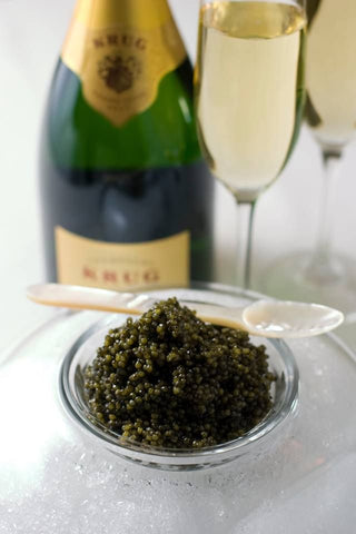a bowl of caviar is in front of a wine
