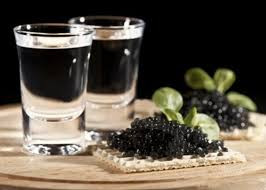 vodka is next to caviar on a biscuit
